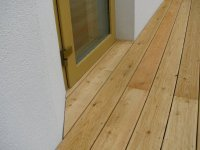 Detail ukončení dřevěné terasy ze sibiřského modřínu a zakončení u vstupních dveří.