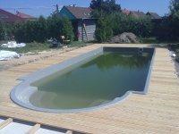 Dřevěná terasa ze sibiřského modřínu kolem bazénu. Kulaté tvary nejsou pro montážníky žádnou překážkou. Sibiřský modřín je nenatřený.
