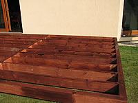 Podkladní rošt z trámů a fošen. Vrchní pokládka řešena akátovou terasovkou.